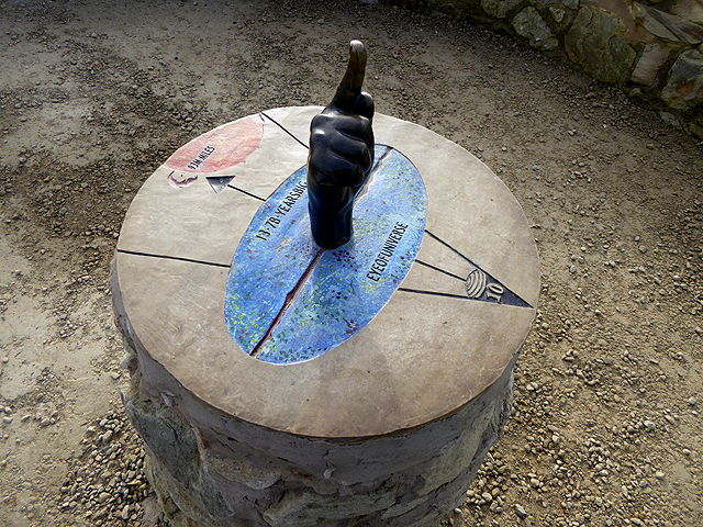 Image of a strange round stone with markings of a triangle and overlapping oval, plus a central post-is it sundial?